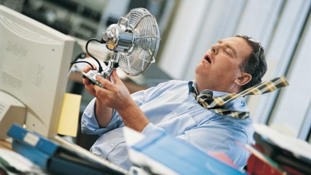 Büromitarbeiter hält sich einen Ventilator vor das Gesicht